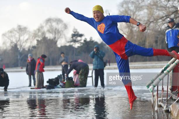 A winter swimming enthusiast dressed like superman jumps into the cold waters of Beiling Park on December 15 2017 in Shengyang Liaoning Province of...