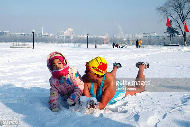 A winter swimming lover and a child lie on snow during New Year celebrations at the Nanhu Park on January 1 2010 in Changchun of Jilin Province China...