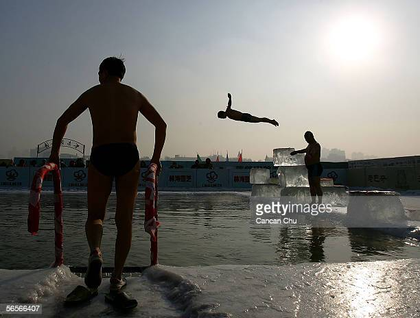 A winter swimming performer dives into a pool carved out of the frozen Songhua river during the 22nd Harbin International Ice and Snow Festival on...