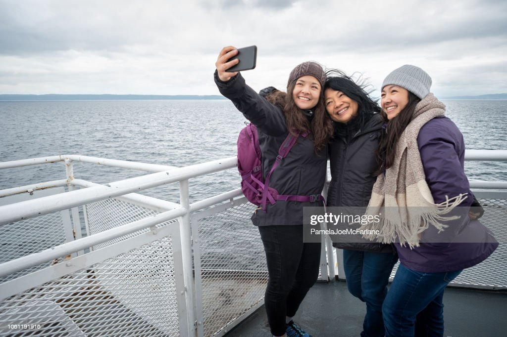Winter Travel on Ferry, Mother and Teen Daughters Taking Selfie : Stock Photo