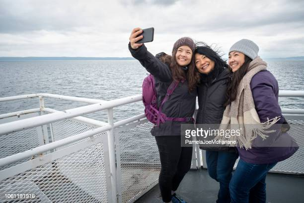 winter travel on ferry, mother and teen daughters taking selfie - vancouver canada stock photos and pictures