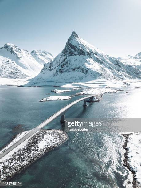 winter view of the bridge at the lofoten islands - snowcapped mountain stock pictures, royalty-free photos & images