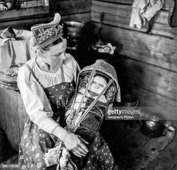 Winter village Skolt Sami woman and her child The mother is wearing a pearl embroidered 'shamtshik'