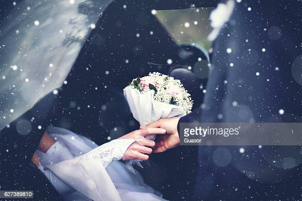 Winter wedding couple groom meets the bride from the car with a bouquet of flowers