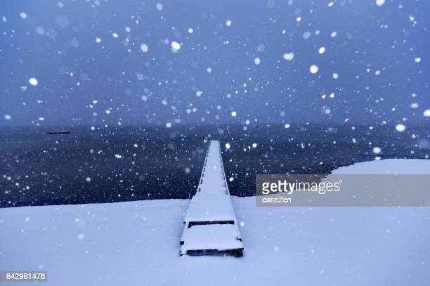 Winter wonderland landscape at Lake Chiemsee with snow-covered jetty and falling snow, Gstadt, Upper Bavaria, Germany
