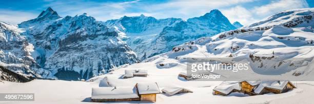 Winter wonderland wooden ski chalets Alpine village snowy mountain peaks