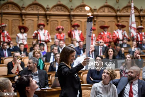 Winter Youth Olympics president Virginie Faivre holds the Lausanne 2020 youth olympic flame during a relay inside the Swiss parliament on the opening...