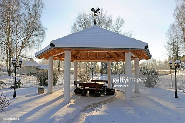 Winterlicher Landhausgarten mit Pavillon und rustikaler Sitzgruppe schneebedeckt