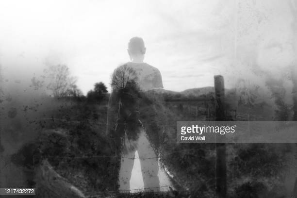 a winters day and a semi transparent male figure standing above a stream in the countryside. with a blurred, textured, weathered, abstract edit. - horror stock pictures, royalty-free photos & images