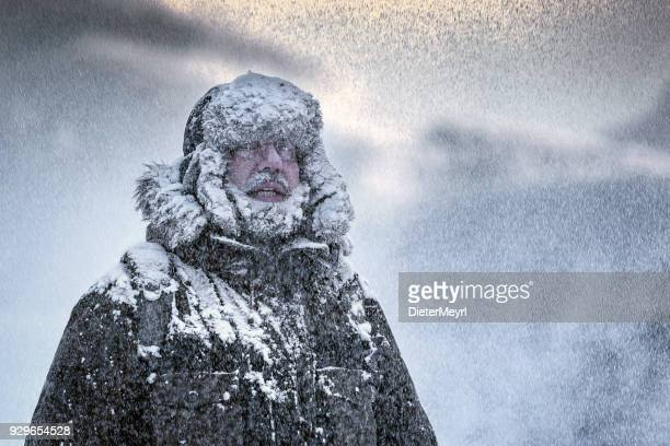 Wintery scene of a man with Furry and full beard shivering in a snow storm