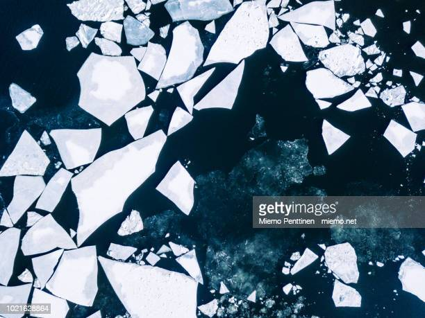 wintery top-down aerial view of cracked ice on baltic sea around helsinki - poolklimaat stockfoto's en -beelden