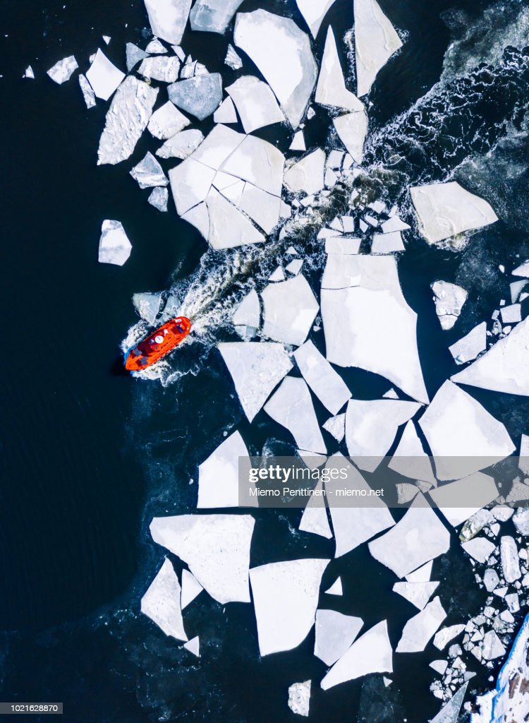 Wintery top-down aerial view of red ice-breaker pushing through cracked ice on Baltic Sea around Helsinki : Stock Photo