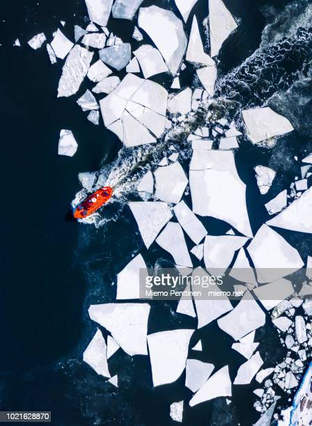 Wintery top-down aerial view of red ice-breaker pushing through cracked ice on Baltic Sea around Helsinki