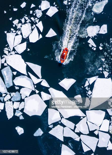 wintery top-down aerial view of red ice-breaker pushing through cracked ice on baltic sea around helsinki - ijsschots stockfoto's en -beelden