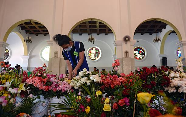 A wioman arranges flowers during a religious festivity in honor of a wioman arranges flowers during a religious festivity in honor of the virgin of guadalupe sciox Gallery