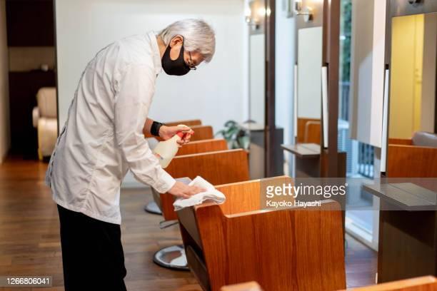 アルコールをこすり美容院でお客様のための椅子を拭きます。 - 消毒薬 ストックフォトと画像