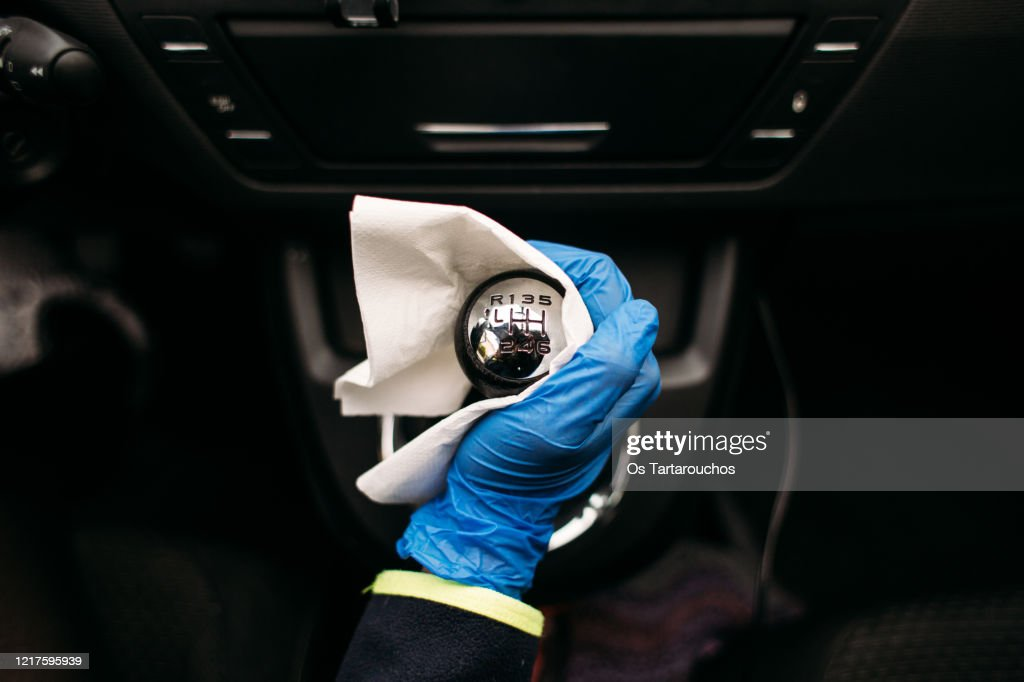 Wiping down gear shift lever in a car : Stock Photo