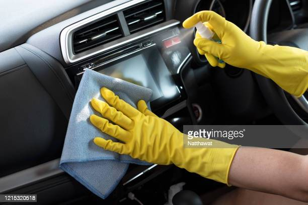 wiping down surface of car dashboard with 70% alcohol spray and disposable damp cloth - disinfection stock pictures, royalty-free photos & images