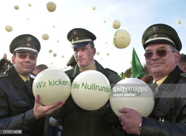 Wir kicken die Nullrunde 2000 weg steht auf den Luftbällen, die drei Polizisten am während einer Protestkundgebung in Berlin zeigen. Rund 1000 Beamte...