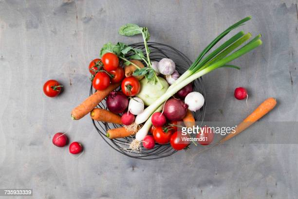 Wire basket with different vegetables on wood