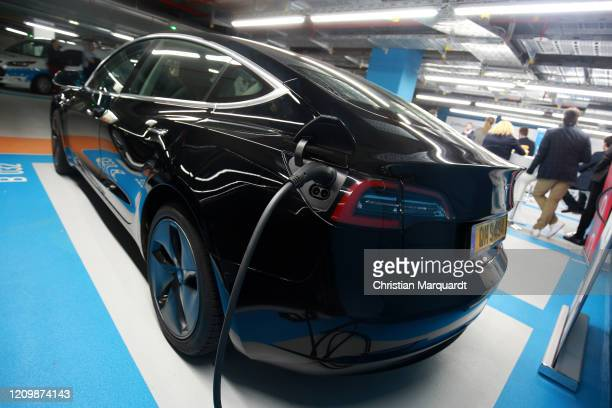 A wire charges a Tesla car during the opening of the first Berlin electric caresharing station of UFODRIVE on March 02 2020 in Berlin Germany...