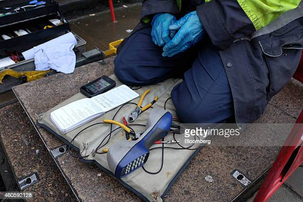 Wire cutters and telephone line testing equipment sits in front of a network engineer from Openreach a unit of BT Group Plc as he prepares to inspect...