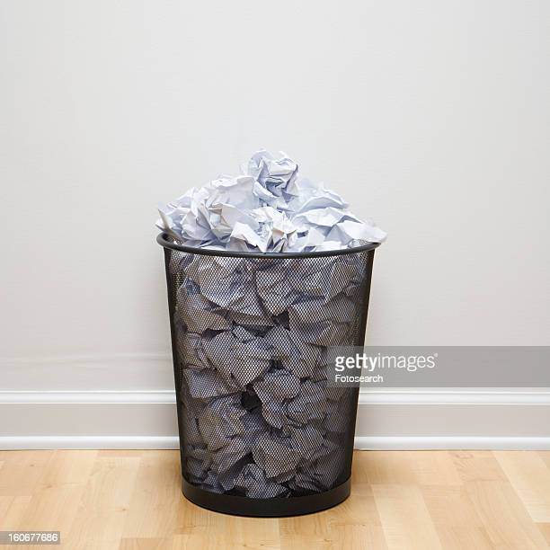 Wire mesh trash can filled with crumpled paper