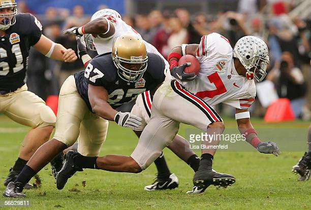 Wire receiver/kick returner Ted Ginn Jr #7 of the Ohio State Buckeyes looks to break a tackle by Marcus Freeman of the Notre Dame Fighting Irish in...
