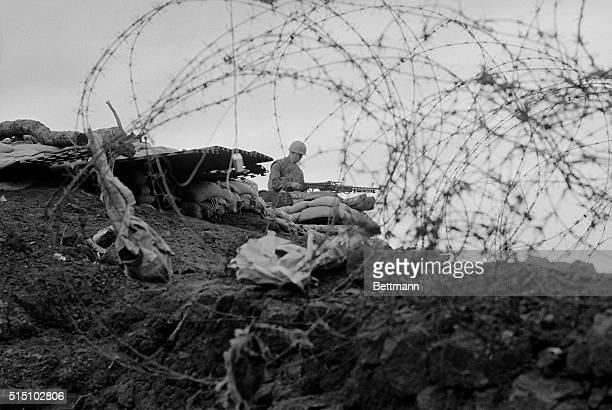 Wired for a Fight Khe Sanh South Vietnam Framed by barbed wire a lone Marine stands guard with a machine gun in a bunker on the perimeter of this...