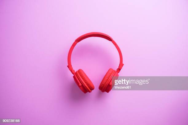 Wireless red headphones on pink background