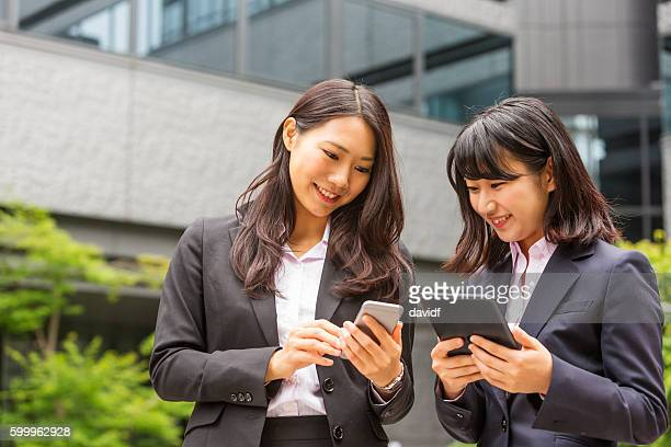 Wireless Technology Being Used by Professional Japanese Businesswomen Working Outdoors