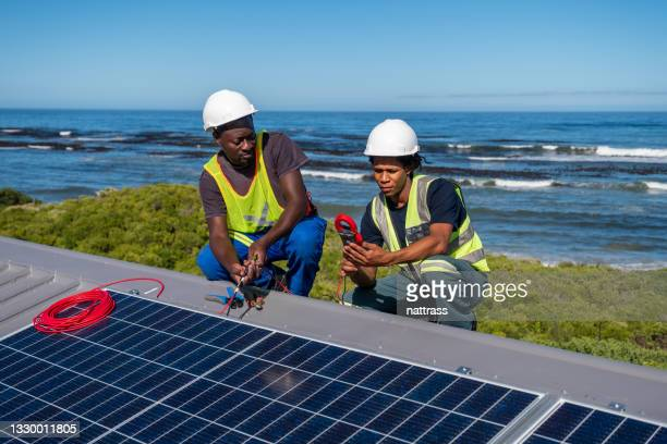 wiring solar panels on a roof - africa stock pictures, royalty-free photos & images