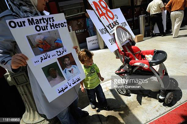 Wisan Baddour stands next to his mother Hazar Nasrini holding a poster showing a picture of Hamza Khatib, a 13-year-old boy who died last week,...