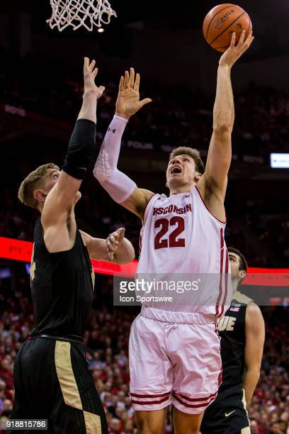 Wisconsin Badger forward Ethan Happ goes up for a layup over Purdue Boilermakers center Isaac Haas during an college basketball game between Purdue...
