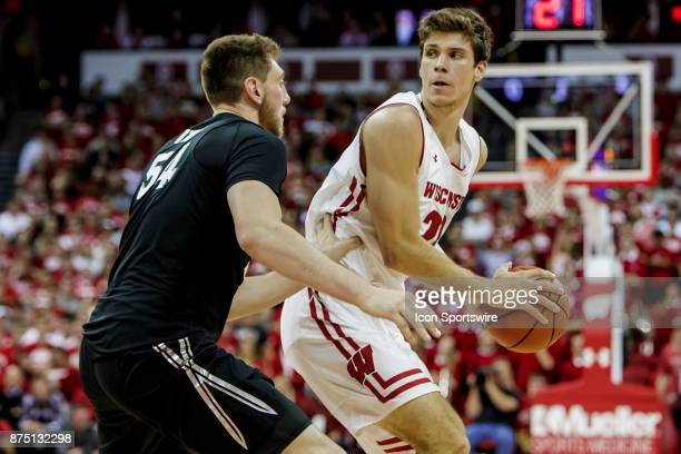 Wisconsin Badger forward Ethan Happ looks to post up Xavier Musketeer player Sean O'Mara durning an college basketball game between Xavier Musketeers...