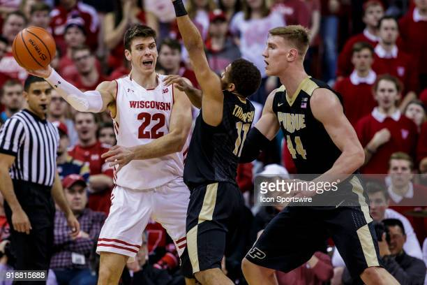 Wisconsin Badger forward Ethan Happ passes out of the double team of Purdue Boilermakers guard PJ Thompson and Purdue Boilermakers center Isaac Haas...