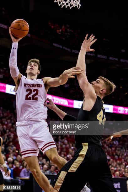 Wisconsin Badger forward Ethan Happ takes and makes a hook shot over Purdue Boilermakers center Isaac Haas during an college basketball game between...