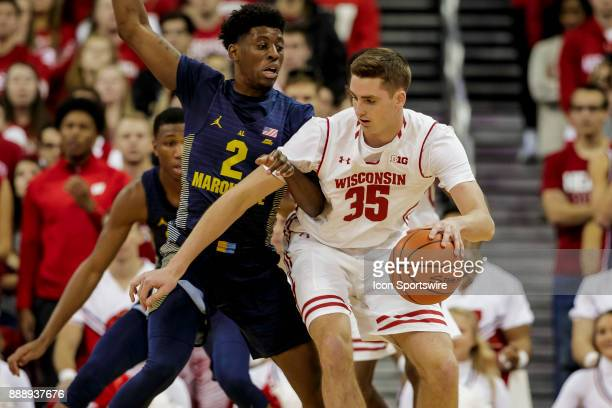 Wisconsin Badger forward Nate Reuvers looks to back down Marquette Golden Eagles guard/forward Sacar Anim during an college basketball game between...