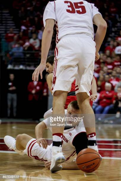 Wisconsin Badger guard Kobe King passes the ball through the legs of Wisconsin Badger forward Nate Reuvers during an college basketball game between...