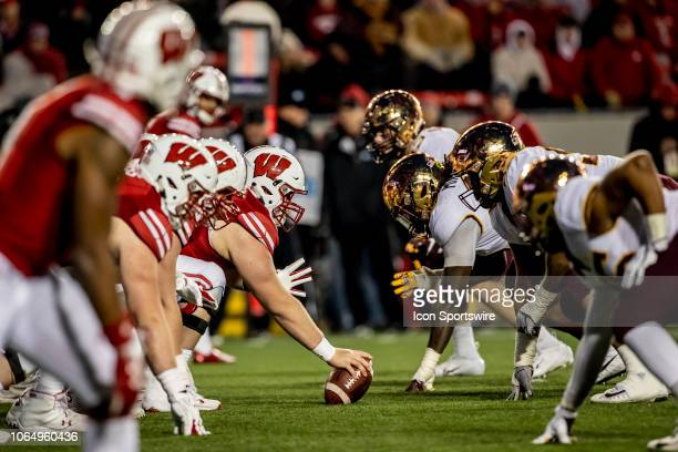 Wisconsin Badger offensive line reads to snap the ball against the Minnesota Golden Gopher defense during an college football game between the...