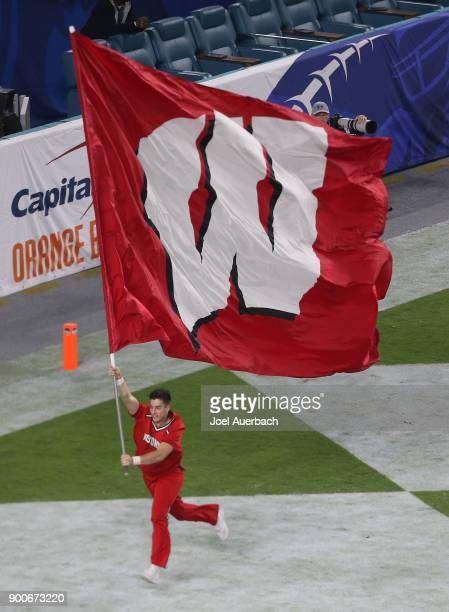 Wisconsin Badgers cheerleader runs the team banner through the end zone after the team scored on a field goal against the Miami Hurricanes during the...