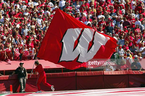 Wisconsin Badgers cheerleader runs with the school banner during the NCAA football game against the Arizona Wildcats on September 21 2002 at Camp...