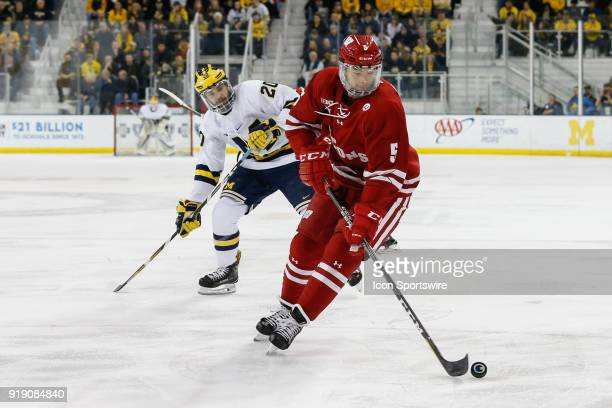 Wisconsin Badgers defenseman Tyler Inamoto skates with the puck against Michigan Wolverines forward Cooper Marody during a regular season Big 10...