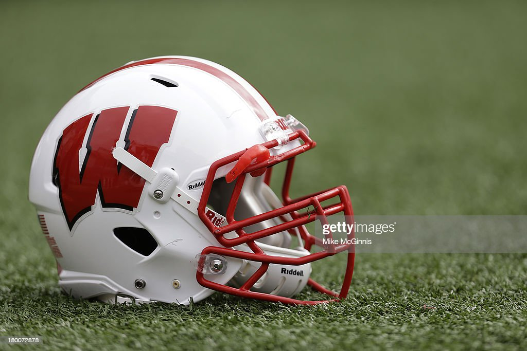 A Wisconsin Badgers Football Helmet Sits On The Field Before