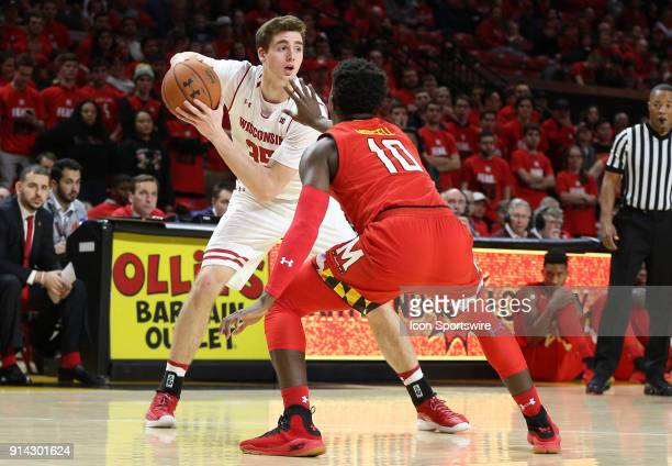 Wisconsin Badgers forward Nate Reuvers holds the ball away from Maryland Terrapins guard Darryl Morsell during a Big 10 men's basketball game between...