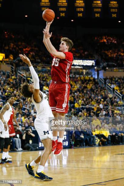 Wisconsin Badgers forward Nate Reuvers shoots a jump shot over Michigan Wolverines guard Jordan Poole during a regular season Big 10 Conference game...
