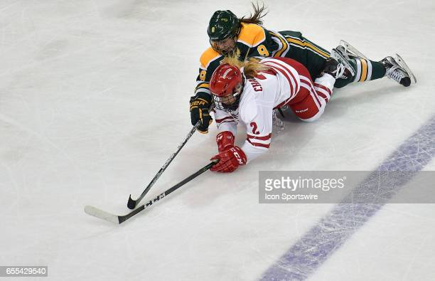 Wisconsin Badgers goalie Melissa Channell and Clarkson forward Genevieve Bannon fall to the ice while going after the puck during the Women's...