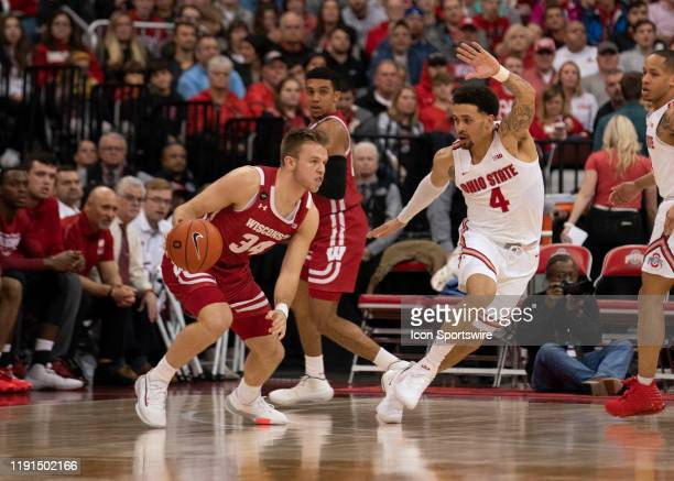 Wisconsin Badgers guard Brad Davison dribbles the ball while being guarded by Ohio State Buckeyes guard Duane Washington Jr during the game between...