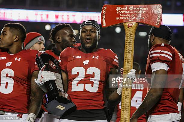 Wisconsin Badgers running back Dare Ogunbowale celebrates with the Big Ten West trophy and Paul Bunyan's Axe after an NCAA Football game between the...