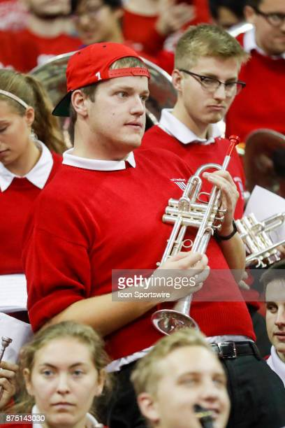 Wisconsin band member plays air guitar on his trumpet during a college basketball game between the University of Wisconsin Badgers and the Xavier...